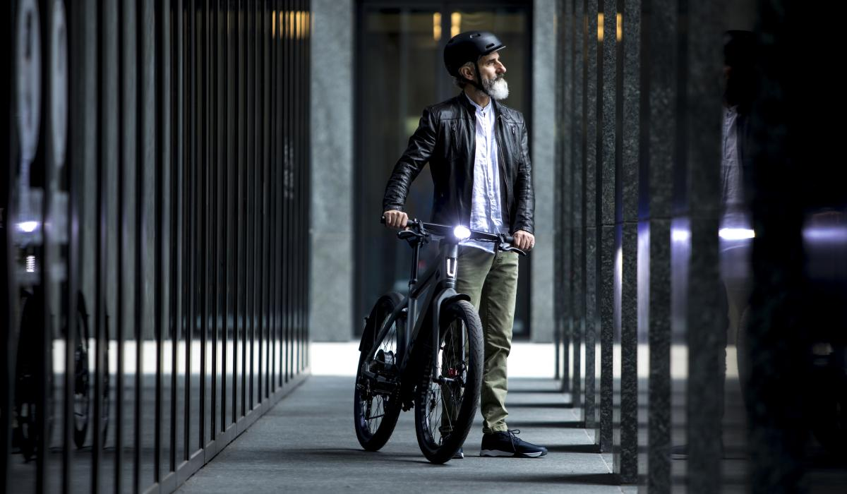 man with stromer bike in front of a building